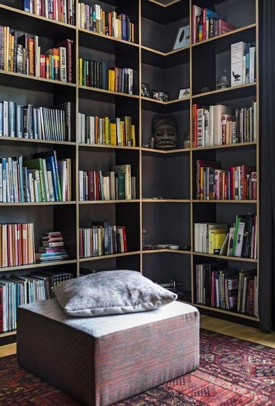 dark cornered book shelves, square ottoman, wooden floor, red rug