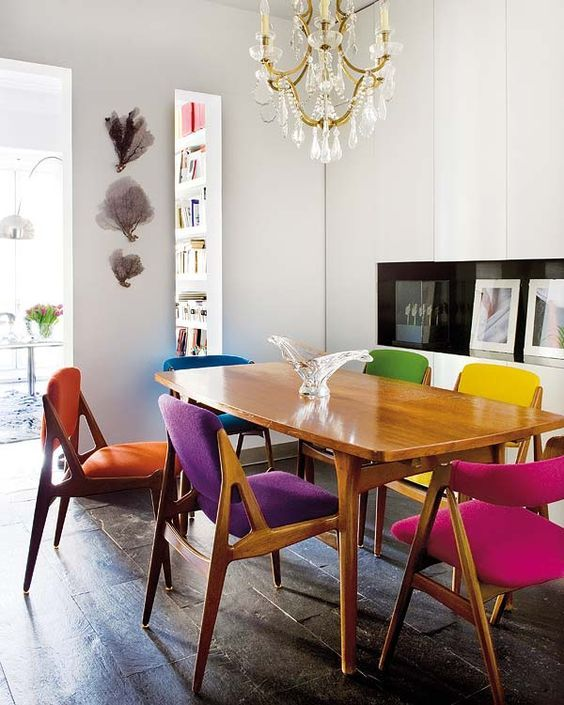 dinin set, glossy wooden table, wooden chairs with colorful jewel tone, white wall, dark wooden floor, chandelier