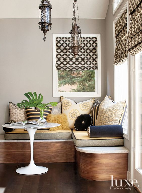 dining corner, curvy wooden bench, yellow cushion, pillows, moroccan pendant, patterned shade, white round table