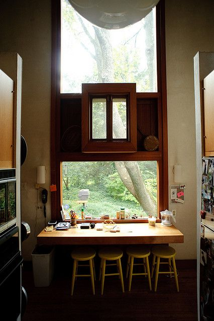 dining nook by the window, tall glass window, wooden window in the middle, wooden floor, floating table, yellow stools, white pendant