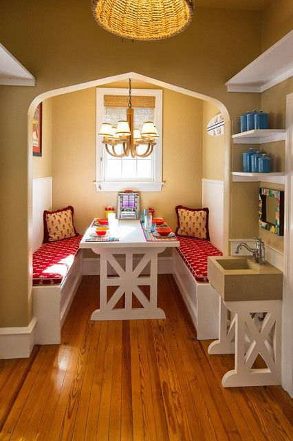 dining nook on alcove, brown painted wall, white bench, white wooden table, chandelier, white framed window, white wooden shelves, brown sink