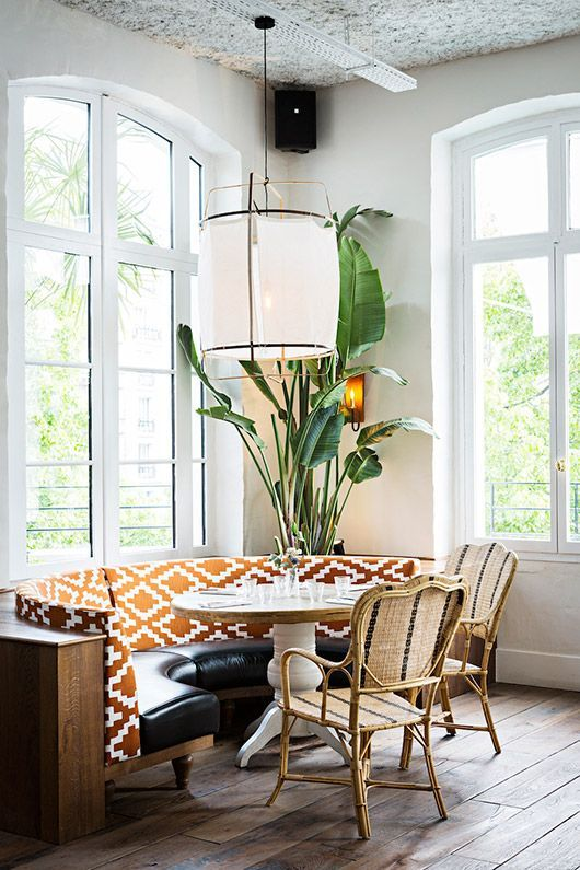 dining nook, wooden floor, half round sofa with yellow patterned back, rattan chairs, white pendant, tall glass window
