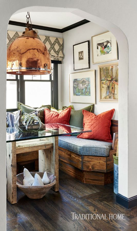 dining nook, wooden floor, white wall, built in wooden bench, wooden table with glass top, copper pendant, plaid shade