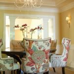 Dining Room, Grey Rug, Pale Yellow Wall, White Wainscoting, Chandelier, Flower Patterned Dining Chairs, Wooden Table