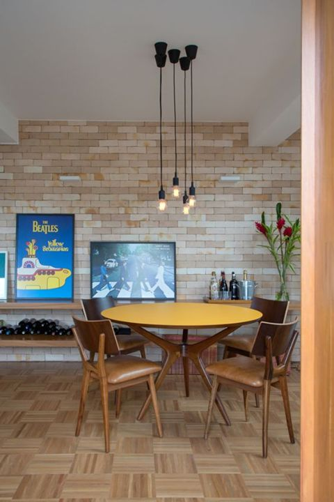 dining room, wooden floor, open brickk wall, floating wine shelves, wooden chairs, yellow top round table, pendant, white ceiling