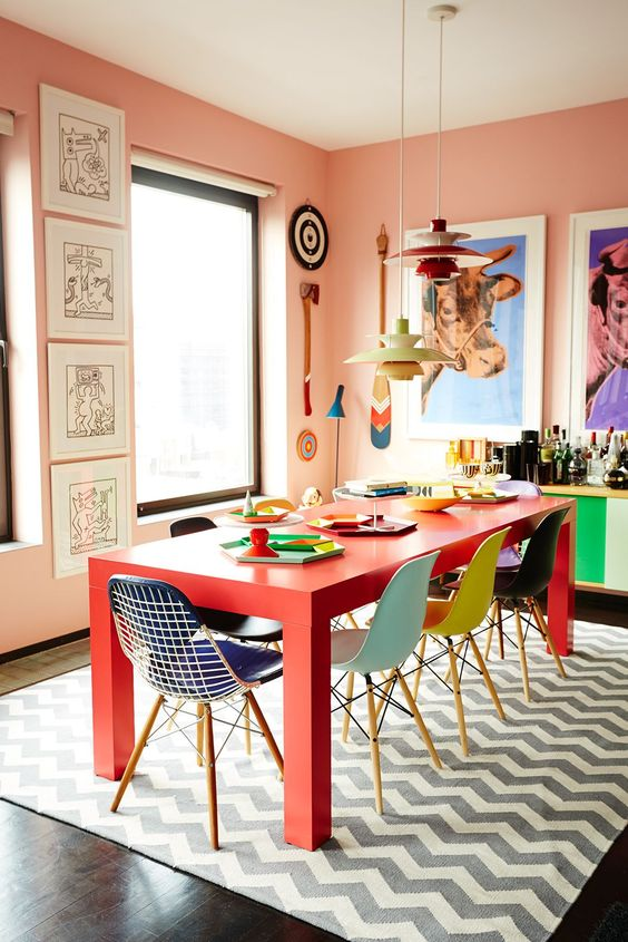 dining set, ret rectangular table, colorful chairs, dark floor, grey white rug, pale peach wall, colorful pendant