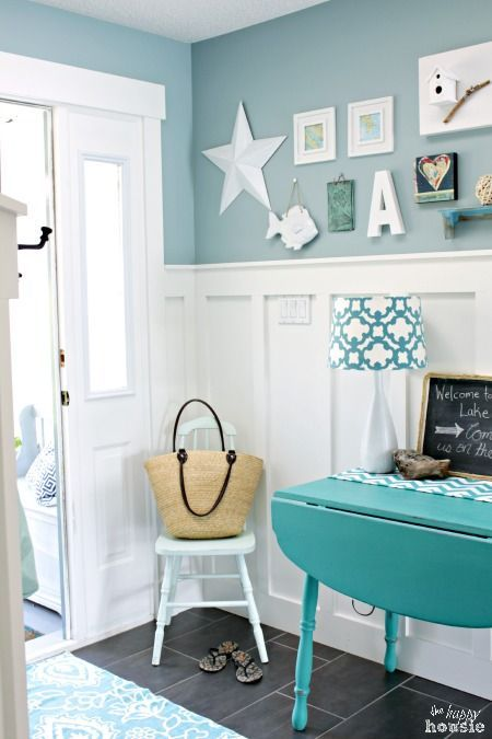 entrance, black floor tiles, blue rug, blue wooden table, white wooden chair, blue wall, white tall winscoting