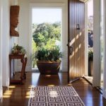 Entrance, Dark Wooden Floor, White Wall, Golden Candelier, Wooden Table, Plants In Brown Pot, Wall Decoration, Brown Rug
