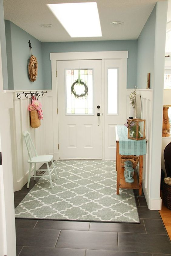 entrance, grey floor tiles, grey rug, blue wall, white tall wainscoting, wooden table, hooks, white wooden chair