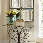 Entrance, Wooden Floor, Blue Rug, Mirror, White Wall, Table With Butterfly Wired Legs Clear Glass Top