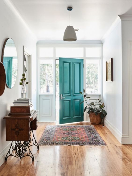 entrance, wooden floor, white wall, pendant, wooden table, black metal legs, round mirrpr, green table
