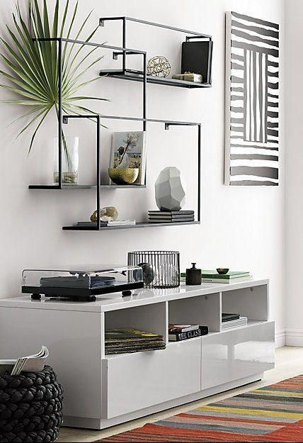 floating black wired shelves, white wooden cabinet, white wall, warm orange rug