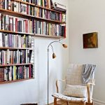 Floating Bookshelves In L, White Wall, Wooden Floor, Floor Lamp With Small Lamp, Rattan Basket, White Woven Leather Chair