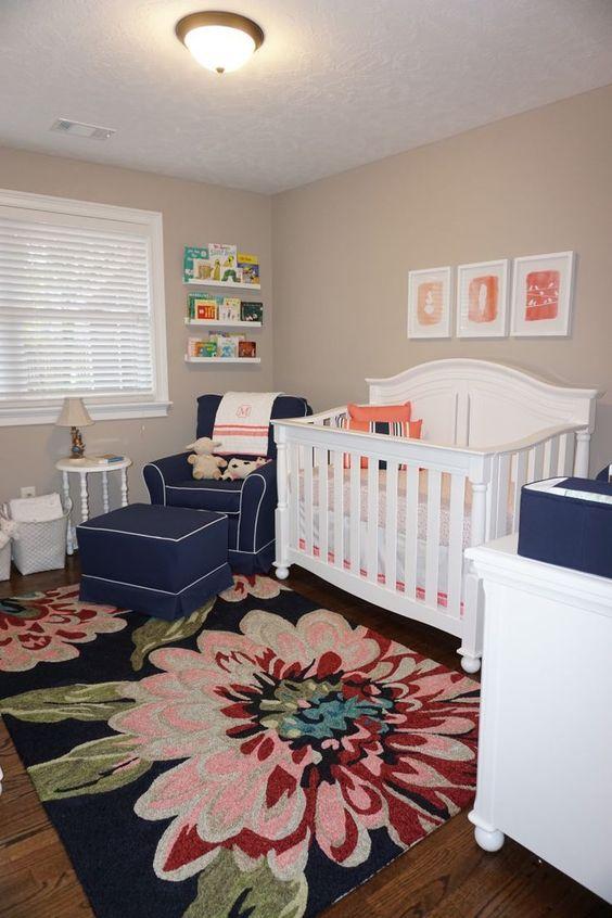 flowery rug, wooden floor, beige wall, navy chair, navy ottoman, white rug