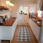 Galley Kitchen, Wooden Floor, White Bottom Cabinet, Wooden Kitchen Top, White Wall, White Backsplash, Floating Shelves, Pendant, Window