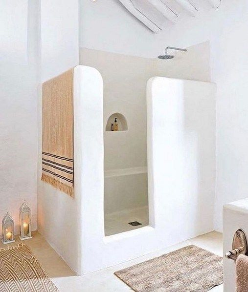 greek bathrom, white plastered wall and floor, built in bench and shelves inside, curvy partition, buit in vanity, rug