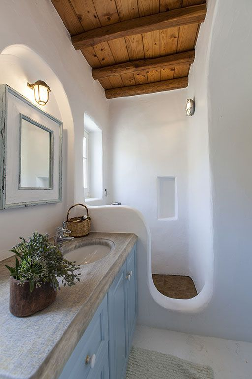 greek bathroom, white plaster wall, curvy partition, window, wooden vanity and top, mirror, sconce, wooden ceiling