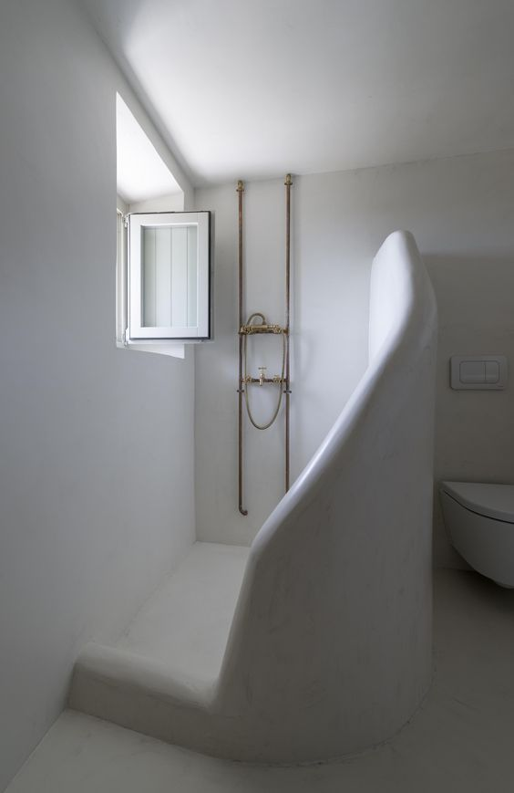 greek bathroom, white plaster wall, sloping partition, window, floating toilet