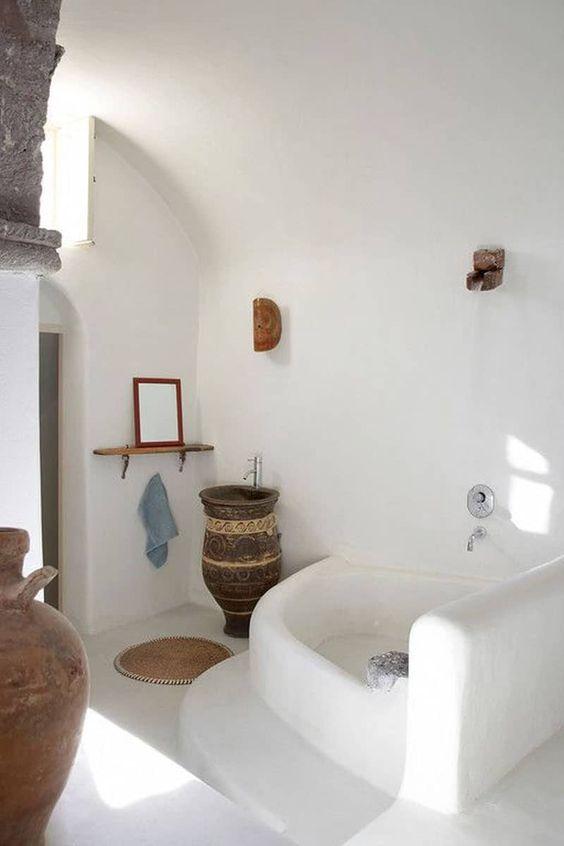 greek bathroom, white plastered bathroom, bath tub, mirror on floating shelves, big earthenware vase