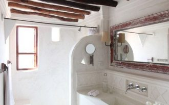 greek bathroom, whtie plastered wall and floor, white ceiling with wooden beams, white built in vanity and sink, rattan basket