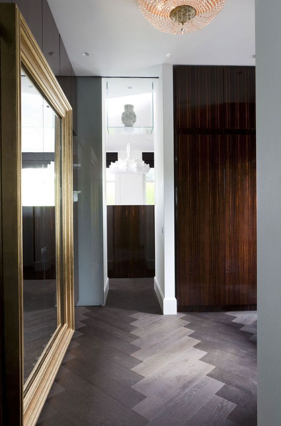 grey combination of herringbone pattern on the floor, large mirror, grey wall, white wall, wooden door