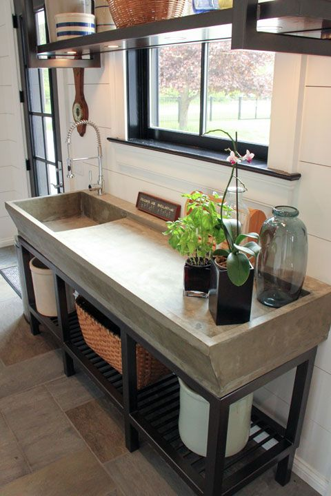 grey sink table, black metal support, white plank wall, black shelves