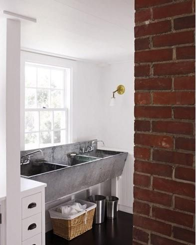 grey sink with three basin, white wall, white ceiling, white cabinet, black floor