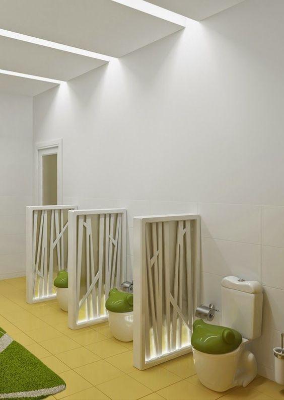 kids toilet, brown floor tiles, white wall tiles, white low partition, whte toilet, green frog cover, LED light