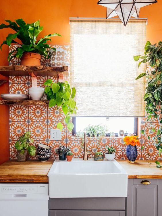 kitchen, orange wall, orange patterned backsplash, wooden kitchen top, white apron sink, grey cabinet, pendant