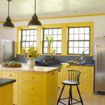 Kitchen, Wooden Floor, Wihte Wall, Yellow Bottom Cabinet, Yellow Island, Grey Kitchen Top Adn Backsplash, Apron Sink, Black Pendant