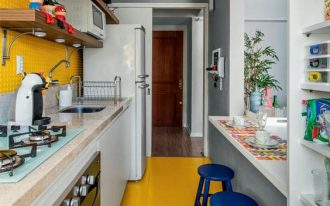 kitchen, yellow floor, yellow square tiny tiles backsplash, white bottom cabinet, wooden floating shelves, grey island with white top, blue stool, white shelves