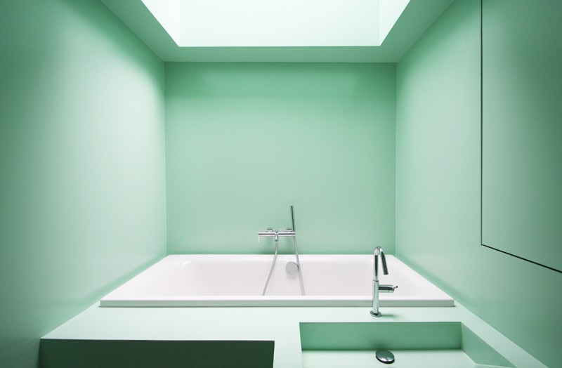 light green bathroom with smooth wall, white tub indented,