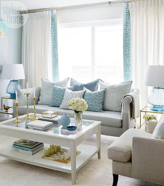 living room, beige rug, white table, beige sofa, white curtain with blue line accent, glass side table,