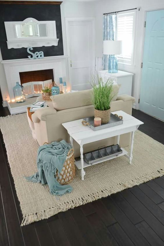 living room, dark wooden floor, rattan rug, beige sofa, white fireplace, white console, black statement wall, white wall, white cabinet, blue glass table lamp