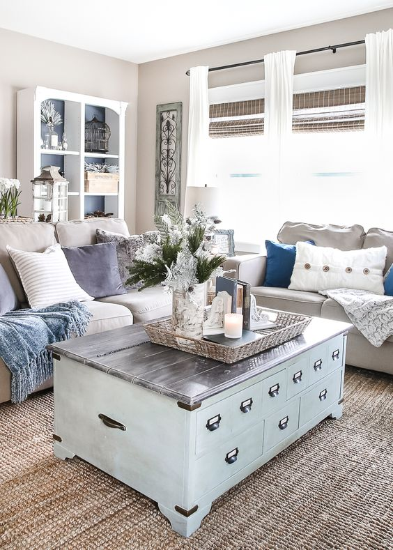 living room, rattan rug, blue wooden coffee table, beige wall, beige sofa, neutral pillows