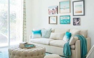 living room, wooden floor, blue rug, beige sofa, blue pillows, beach themed accessories, white tufted round ottoman, white round ottoman, chandelier, glass sliding door
