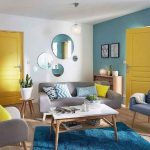 Living Room, Wooden Floor, Blue Rug, Wooden Coffee Table, Blue Wall, White Wall, Round Mirrors, Grey Sofa And Chairs, Yellow Door