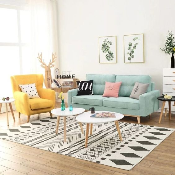 living room, wooden floor, white wall, patterned white black rug, white nesting coffee table, green sofa, yellow chair, white side table