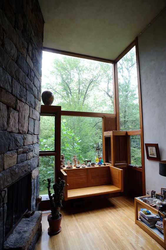 living room, wooden floor, wooden floating seat, glass window, grey wall, coffee table, black stone wall, fireplace