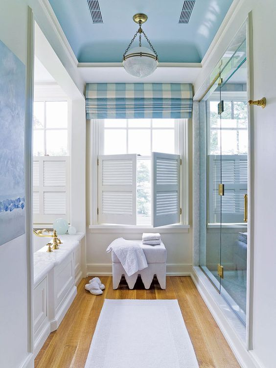 long bathroom, wooden floor, white wall, white marble tub, blue tainted glass, white marble, windows, blue roman shade, blue ceiling arch, white orb chandelier