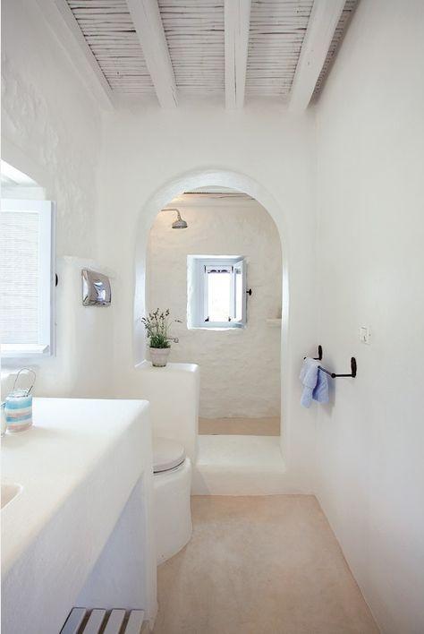 long greek bathroom, white plastered wall, beige floor, curvy arch, white plastered vanity