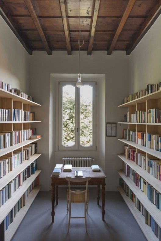 long room with white wall, grey floor, two rows of bookshelves on the side, wooden table and chairs in the middle, window