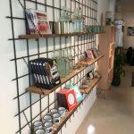 Metal Wall Grid, Wooden Shelves, Wooden Cabinet, Brown Floor