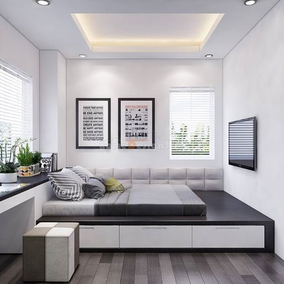 minimalist bedroom, grey dark wooden floor, black bed platform, white storage, bilt in black white table, ottoman, white wall, white ceiling