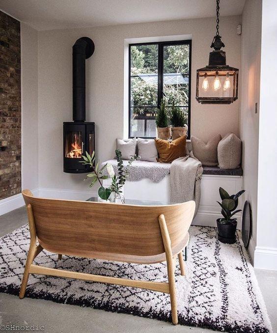 minimalist living room, grey floor, rug, window nook, pillows, hanging fireplace, wooden curvy bench, pendant