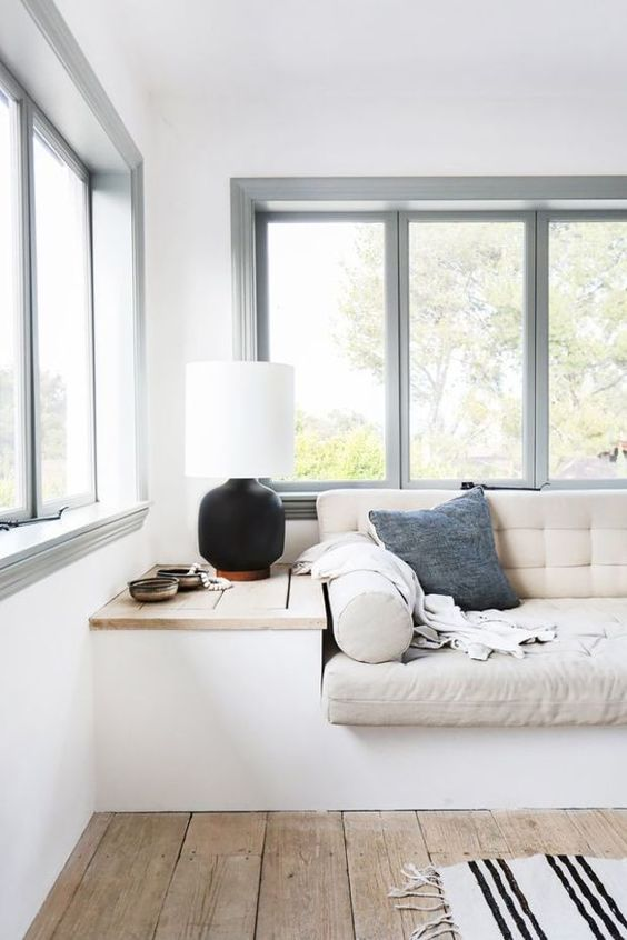 minimalist reading nook, wooden floor, white bench, off white cushion, built in table, black table lamp, glass window