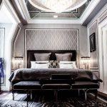Mirrored Ceiling With Crystal Chandelier, Wooden Floor, Black Rug, Black Bedding With Headboard, Grey Wallpaper