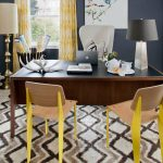 Office Guest Chair Black Table Lamp Wooden Desk Black Top Patterned Rug Floor Lamp Executive Office Chair With High Back Wooden Chairs Window Dark Blue Wall Yellow Curtains