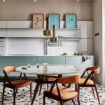 Open Kitchen, Patterned Floor Tiles, Green Ktichen Cabinet, White Backsplash, Floating Shelves, Marble Table, Orange Chairs