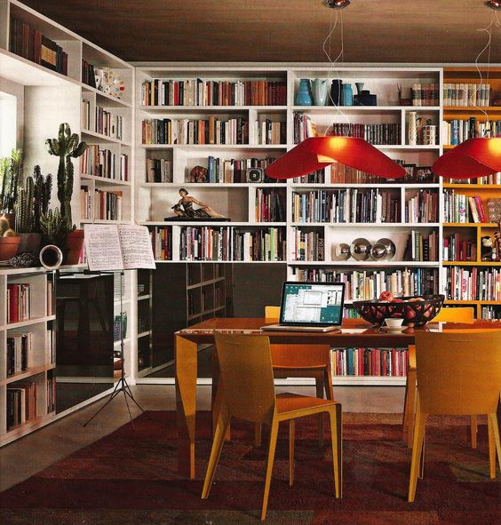 open library, brown floor, white wooden shelves, wooden table, wooden yellow chairs, orange pendants, orange rug